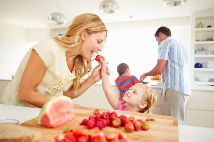 Une mère et son enfant mangeant des fraises fraîches