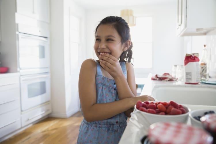 Meisje in de keuken met een kom frambozen en vershoudfolie